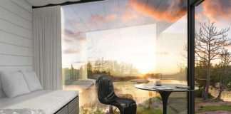 A sun room with walls made of glass looks out onto a lake surrounded by a forest as the sun sets.