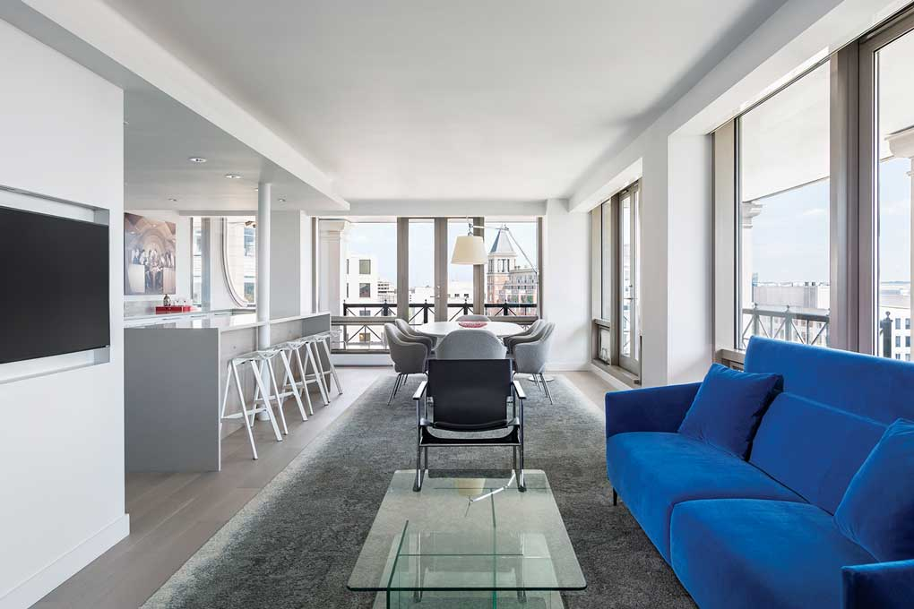 A living room built by U+B Architecture that features a small table with chairs surrounding it, a blue sofa and floor-to-ceiling windows.