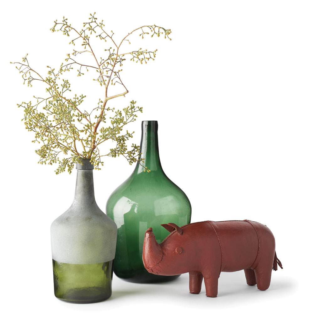 A Leather Smith rhino is set against two antique glass bottles.