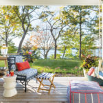 Porch overlooking Lake Minnetonka with a porch swing and chair and drink cart.