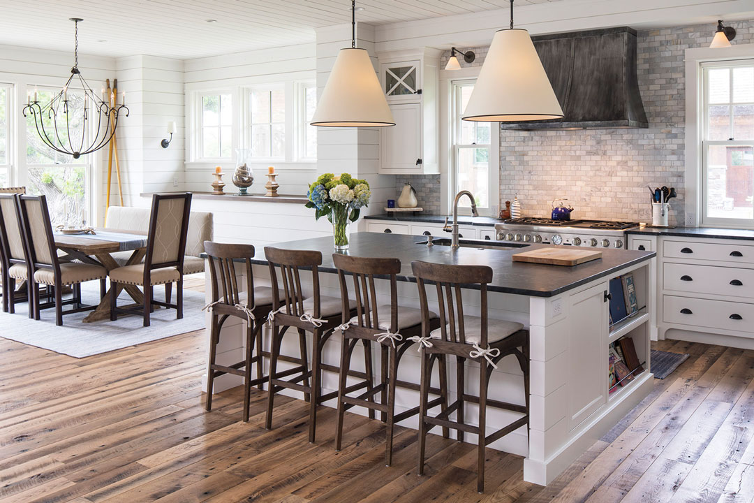 An elegant kitchen features a center island with overhanging lights, and a dining room table is off to the left with a chandelier hanging overhead.
