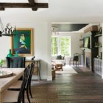 A great room with a dining room table in the foreground and living room in the background. All throughout is random-plank, cerused white oak flooring and reclaimed timbers.