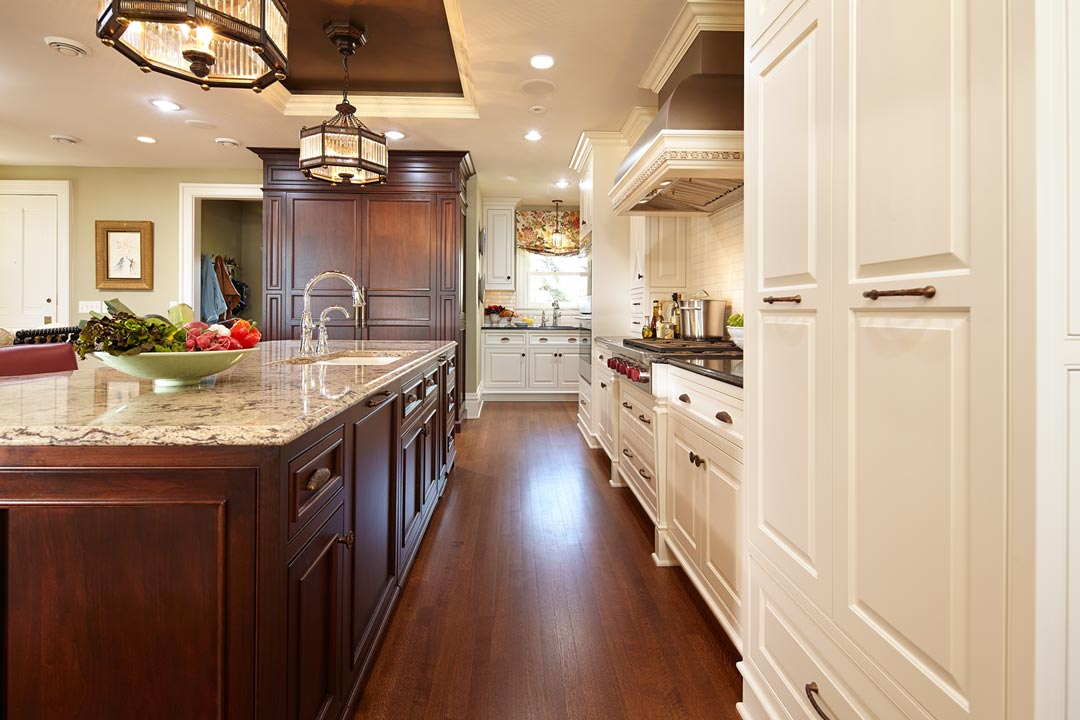 A kitchen with hardwood floors, white cabinetry and chandeliers hanging above the center island.