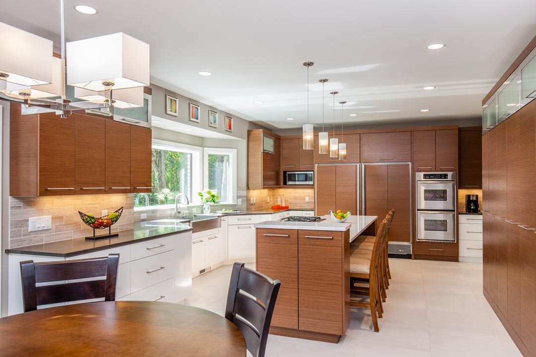 A kitchen featuring stainless steel appliances, white and brown cabinetry, and lights hanging above the center island.