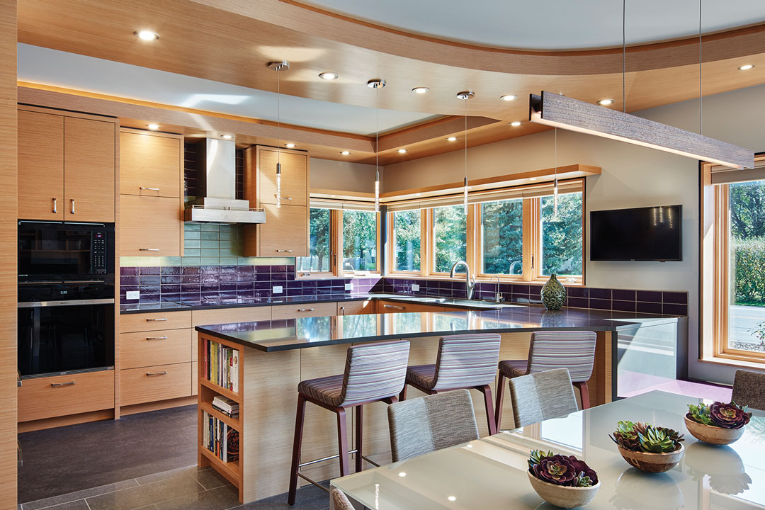 A kitchen designed by LiLu Interiors shows a center island with high chairs on one side, light wood cabinetry, tile backsplash, mounted television, and dining table.