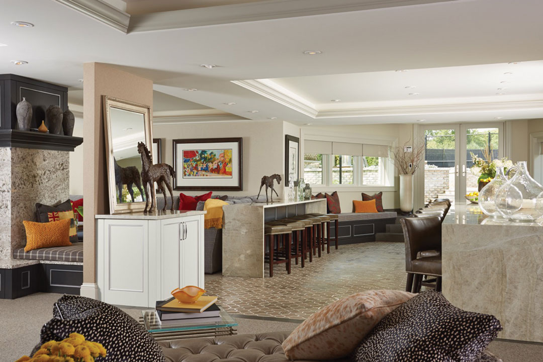 A living room designed by Mint Design features horse statues, bar, seating and colorful pillows.