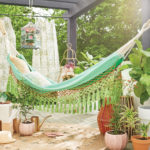 A hammock surrounded by plants and Mediterranean decor.