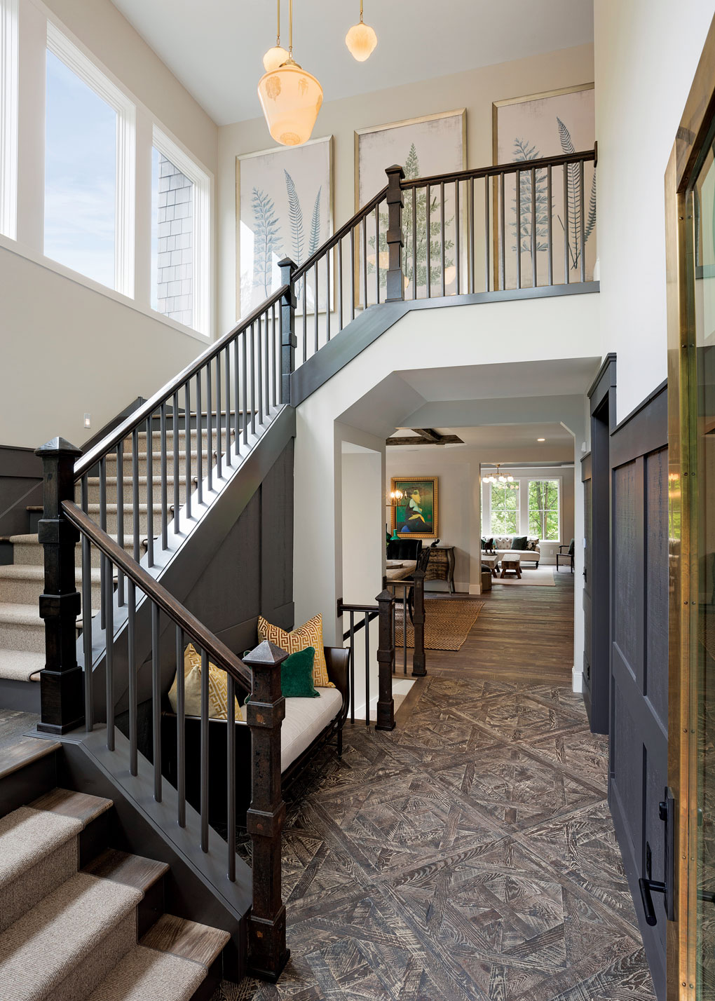 The entry is distinctive, from the brass-wrapped front door to the customized finish of the parquet flooring to the salvaged newel posts and vintage milk-glass lighting that hangs overhead.