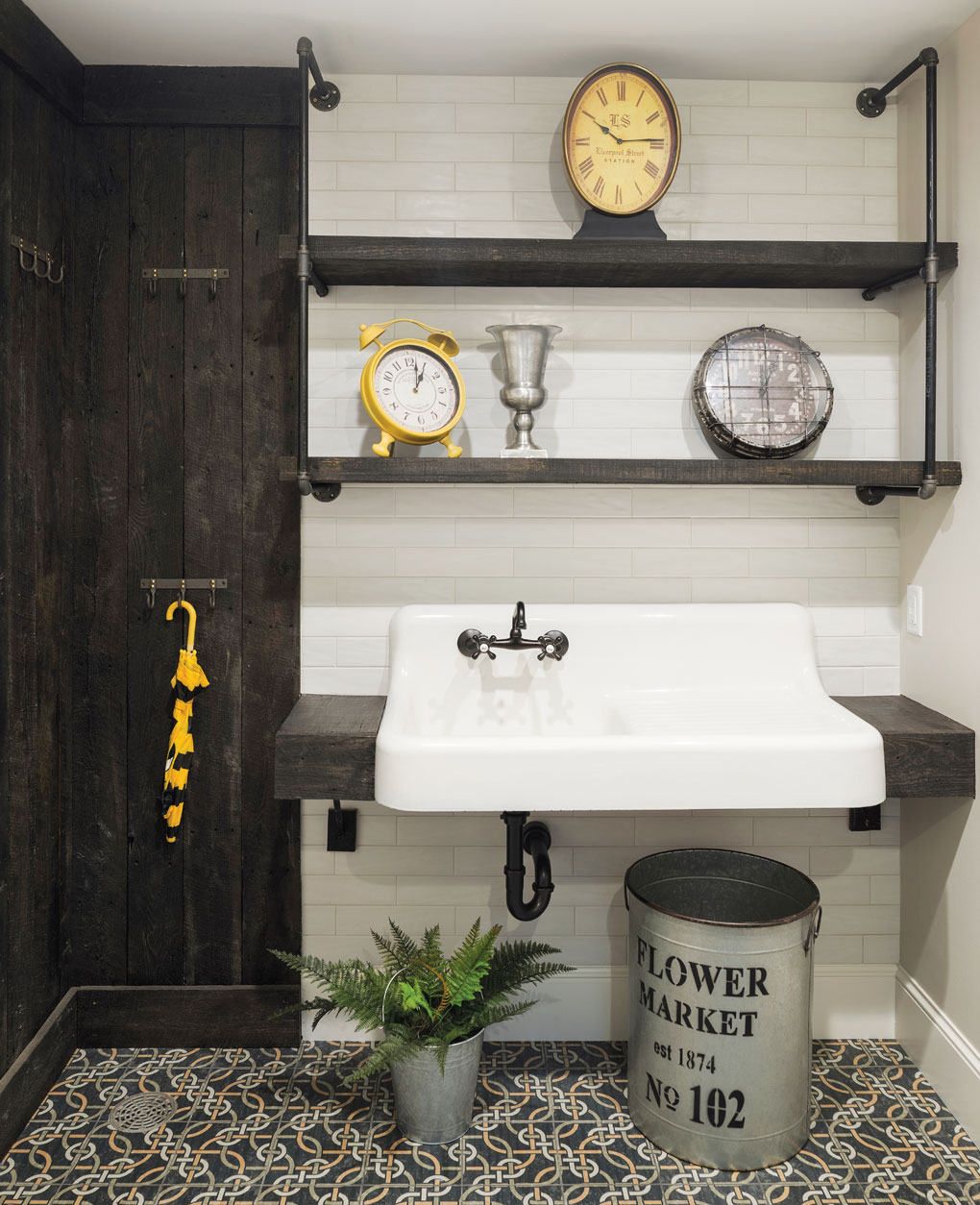 A mudroom with three clocks adorning the shelves above a large sink. An umbrella hangs on a nearby wall.