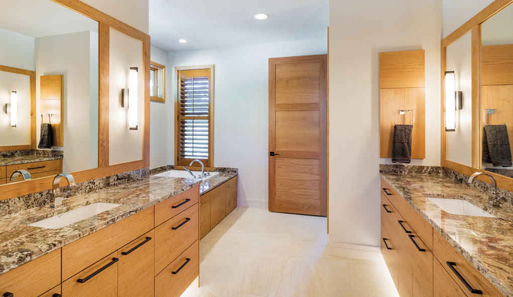 A master bath features twin vanities and sinks on each side of the room. A soaking tub lies beyond.