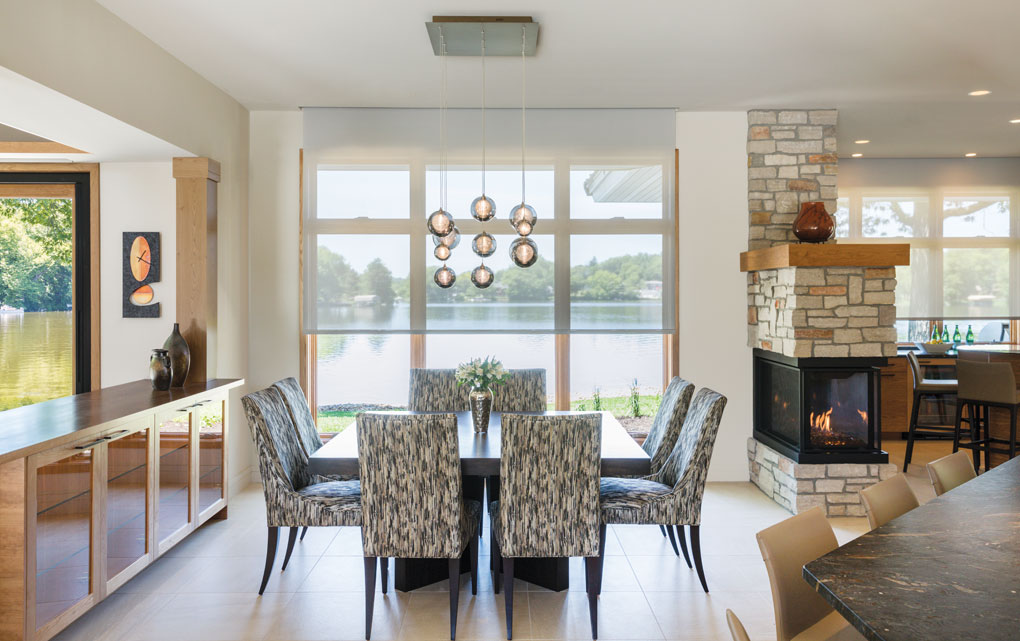 The Kadur pendants above the custom dining table add sparkle to the view of the river.