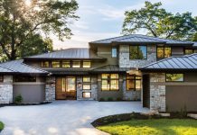 The house shows off its views of the water from every side. Glass doors, metal roof, stucco, and stone make it beautiful as well as low maintenance.