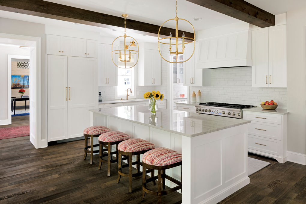 The kitchen boasts a quartzite island with seating for four and white cabinetry.
