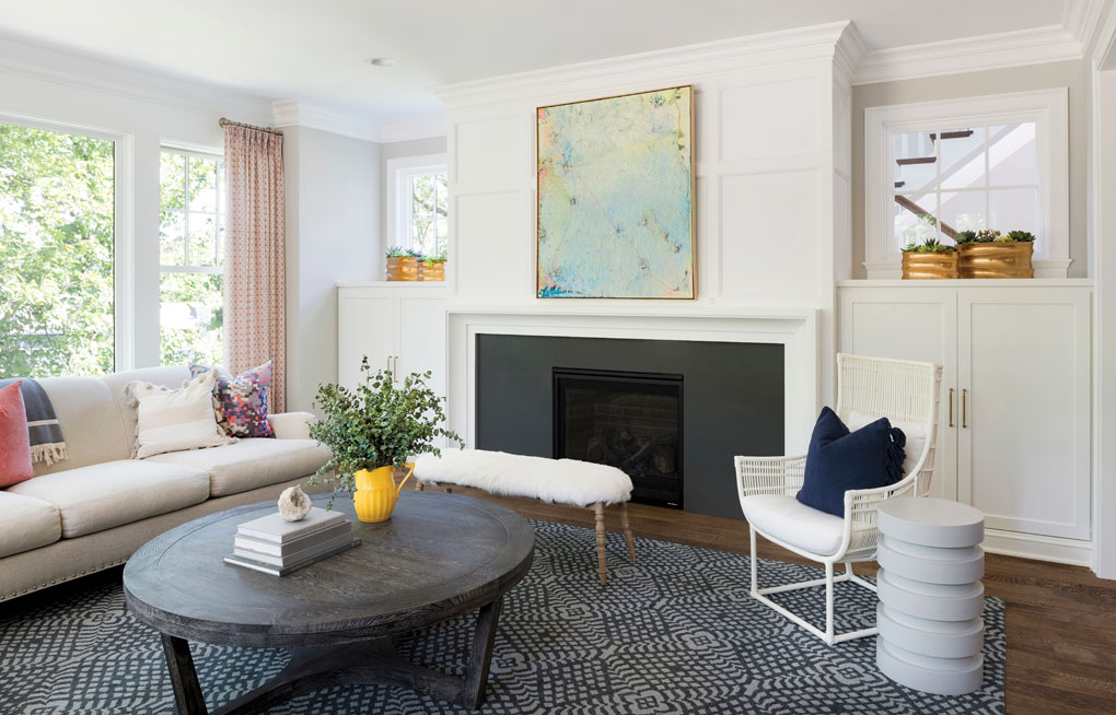 The cottage-style living room features fresh white paneling, millwork, and bookcases.