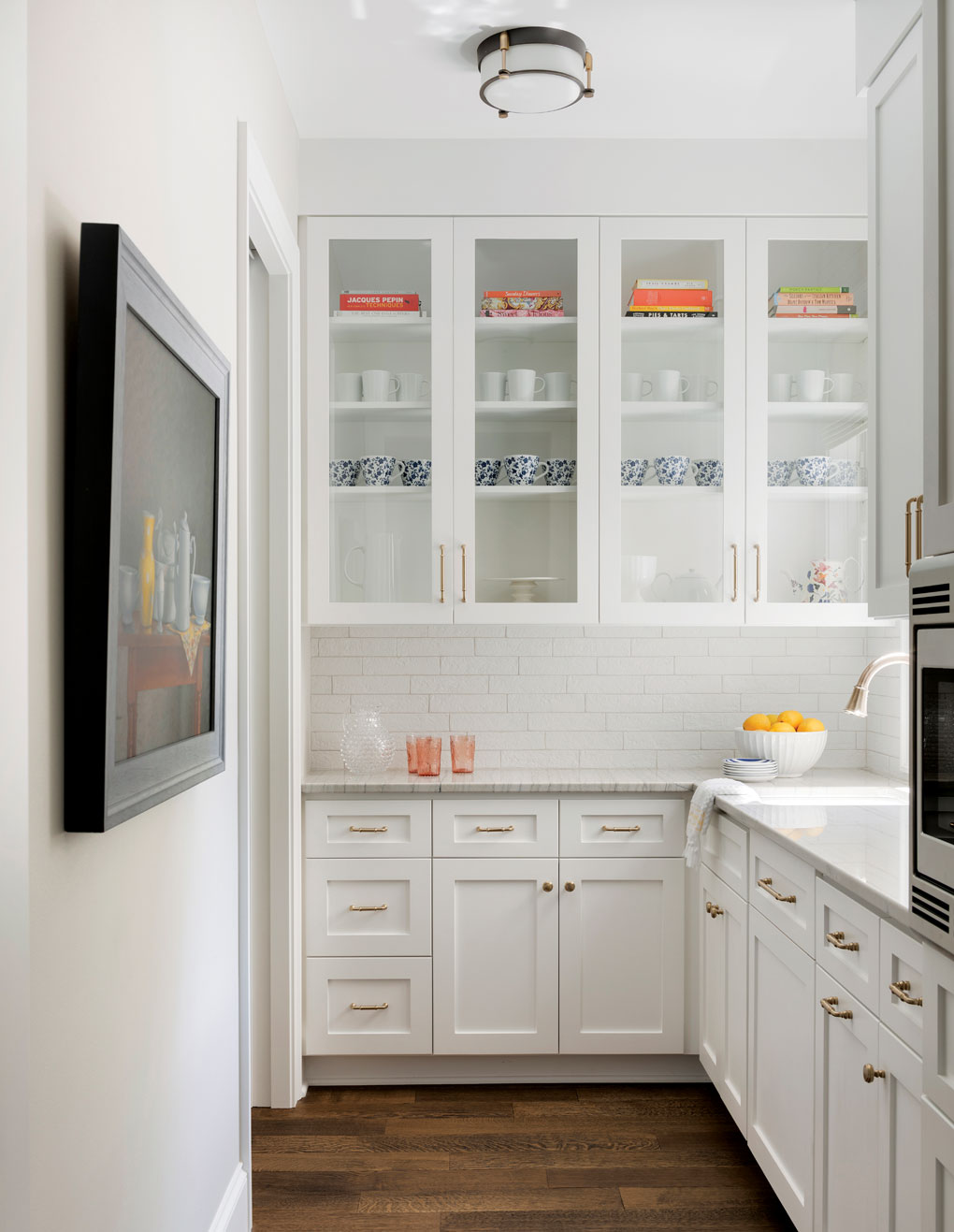 The adjacent pantry/galley keeps prep messes out of sight and features white cabinetry.