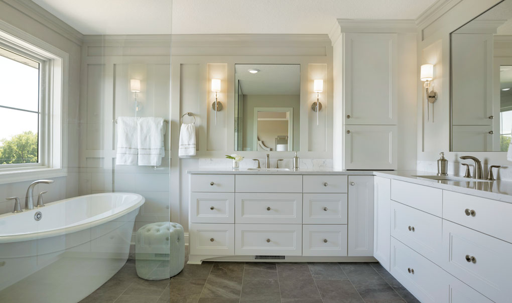 A master bathroom features an inviting soaking tub, glass walk-in shower, twin vanities and white cabinetry.