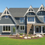 The exterior of a large, blue custom home with landscaping, large windows, and a large front porch.