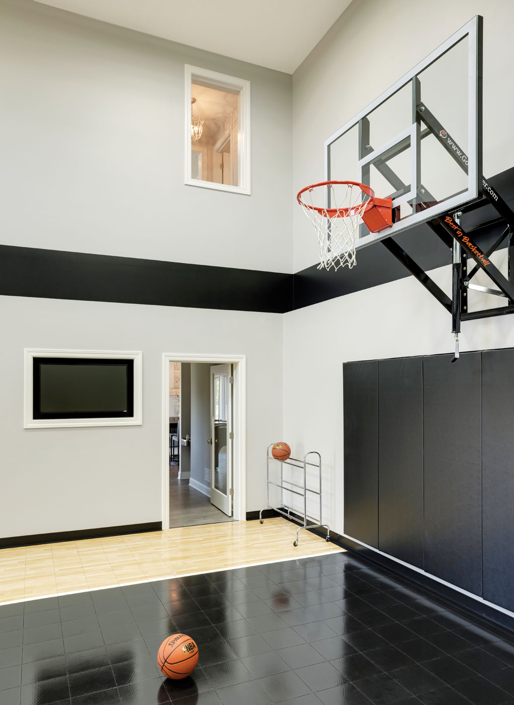 An indoor sport court shows a basketball hoop with basketballs ready to be played with.