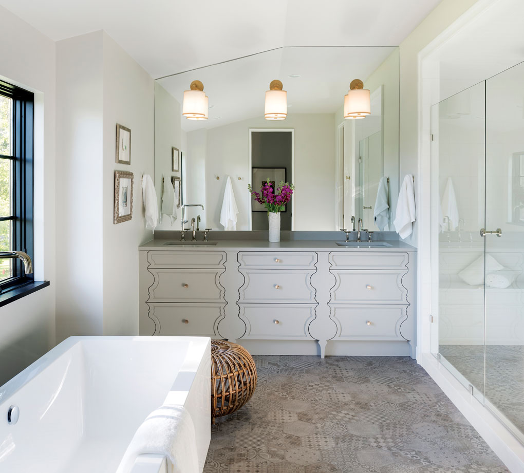 A master bathroom features his-and-hers sinks, ceramic-tile floors, a walk-in shower, and a soaking tub.