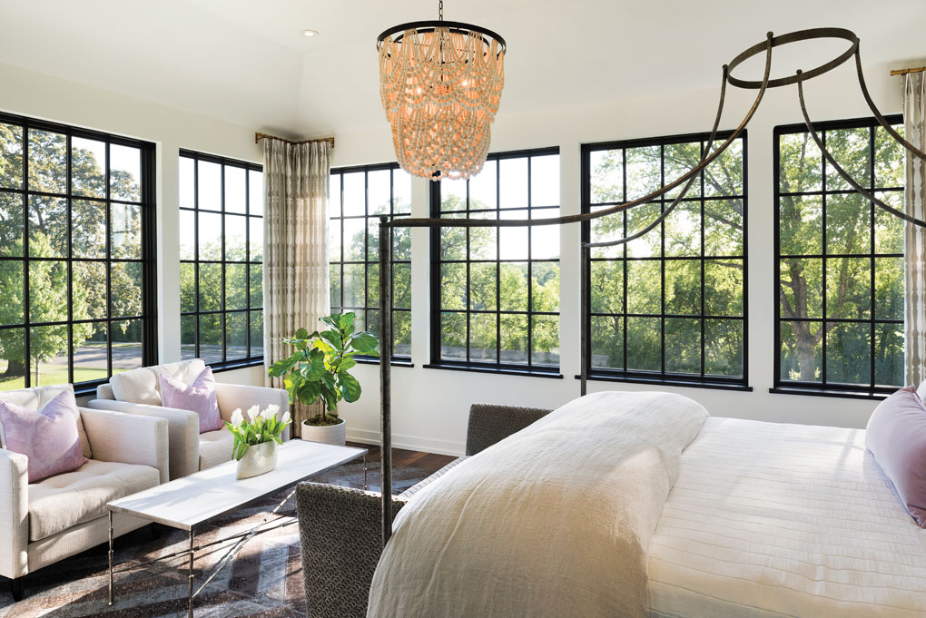 In the master bedroom, black-framed windows showcase 270-degree views of the trees and river.