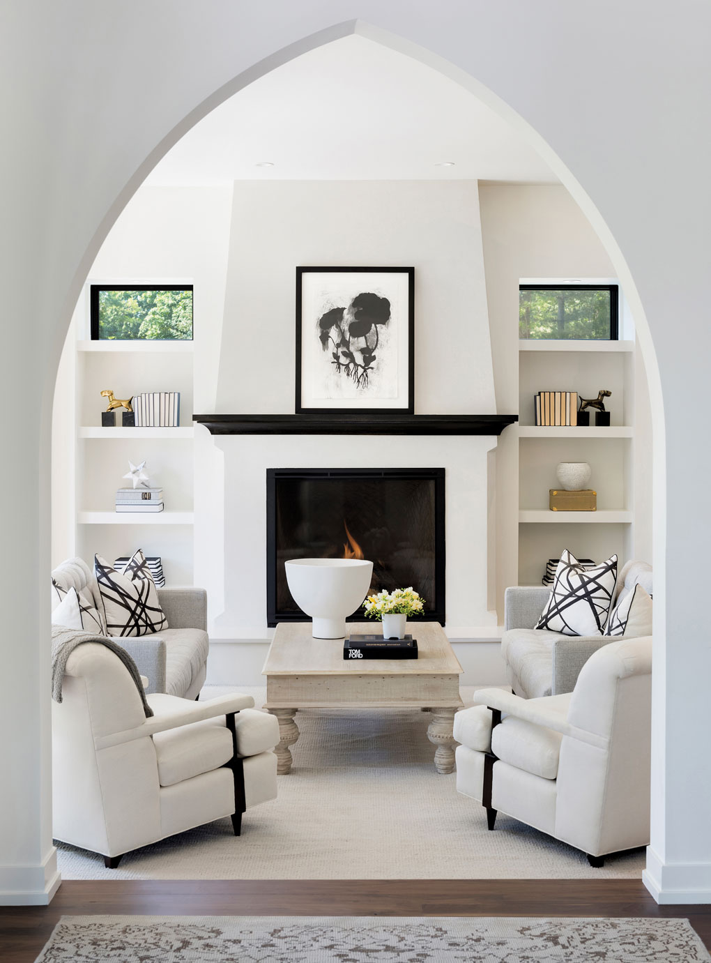 A living room with white furniture surrounding a coffee table set beside a fireplace is seen through an archway.