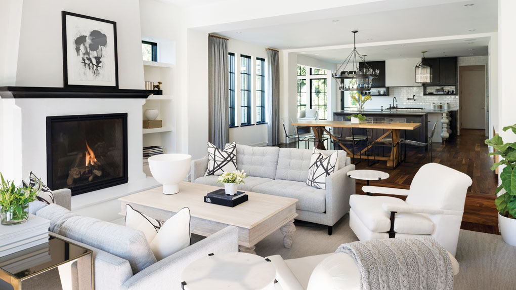 A living room with a coffee table surrounded by chairs and a fireplace lies adjacent to the kitchen featuring a white subway tile backsplash, ebony-stained walnut cabinets, quartz-topped island, and stylized turned-wood legs.