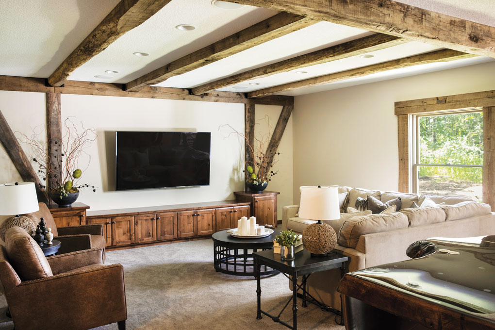 A basement with exposed timber beams on the ceiling, a large television on the far wall, two couches and two chairs.