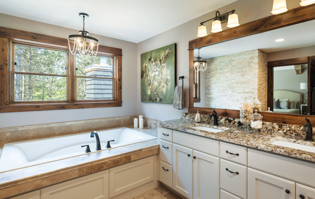 A bathroom with twin sinks on a large vanity with a stone countertop is set beside a large master bath with a chandelier overhead.