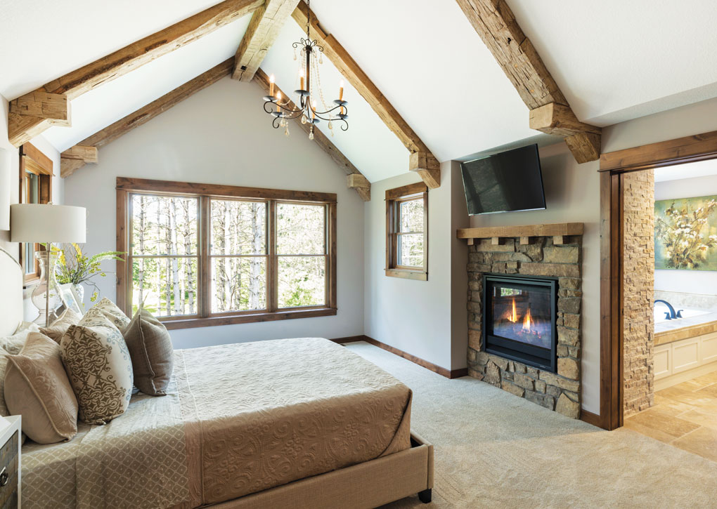 A master bedroom with a vaulted ceiling lined with exposed timber beams overlooks a stone fireplace and large bed.