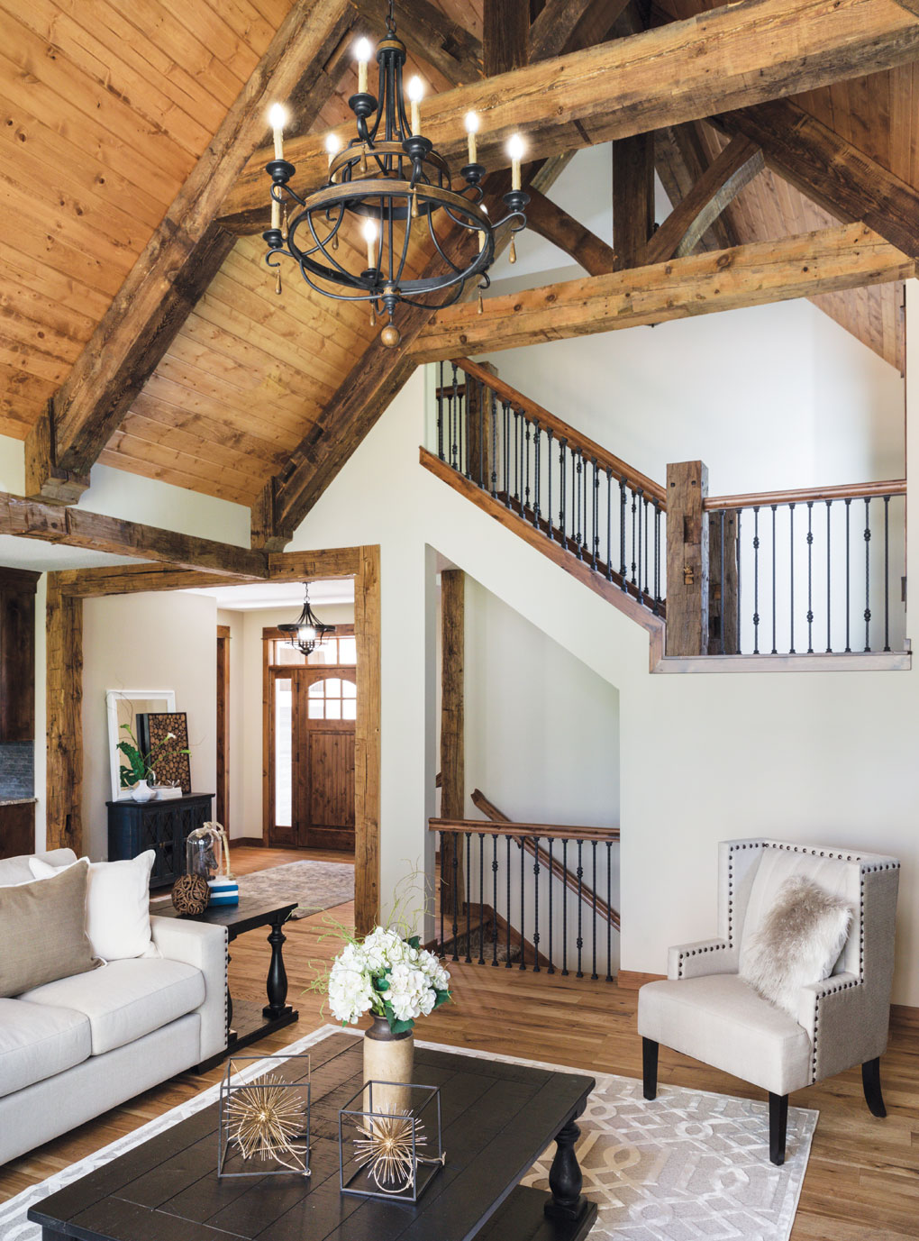 A living room and staircase featuring a vaulted ceiling, reclaimed trusses, hand-hewn newel posts, and wrought-iron railings give the room a mountain-lodge vibe.