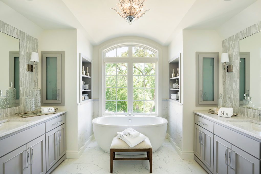 A large master bathroom is flanked by twin vanities on both sides that lead to a large soaking tub that overlooks the yard accented with large trees.