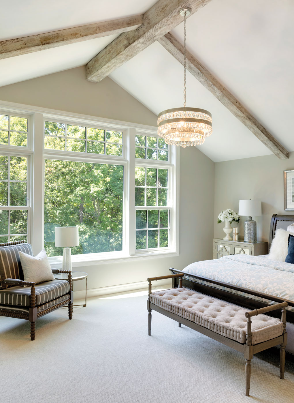 Rustic wood beams line the high ceiling that overlooks a large bed and chair inside a master bedroom. Large windows also look out onto trees on the far wall.