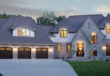 The exterior of an Edina, Minnesota home with arched windows, dormers, pitched roofs, stone, and stucco.