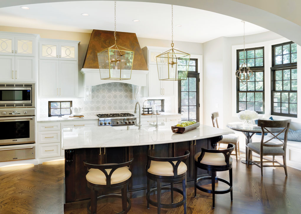 A kitchen with hardwood floors features white cabinetry, stainless steel appliances, a large range hood, and center island. A nook is off to the right with windows overlooking the yard.