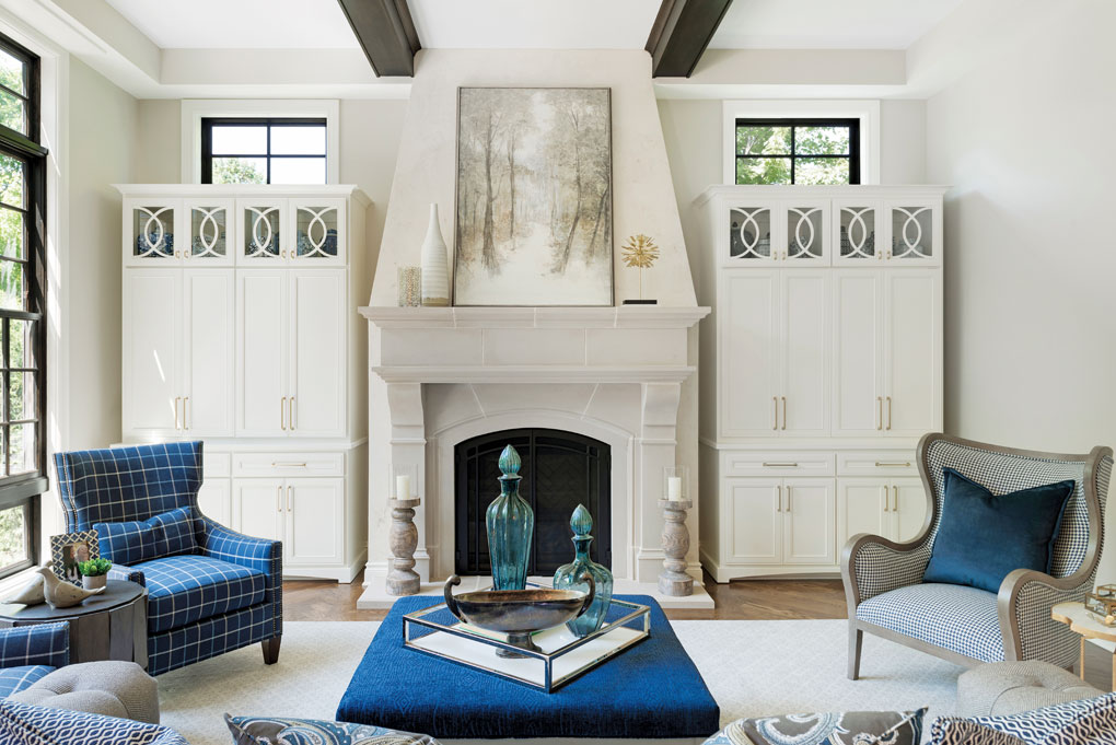 A living room highlighted by a large Venetian plaster fireplace that is flanked by large white cabinets, and a blue coffee table and chairs are set next to it.