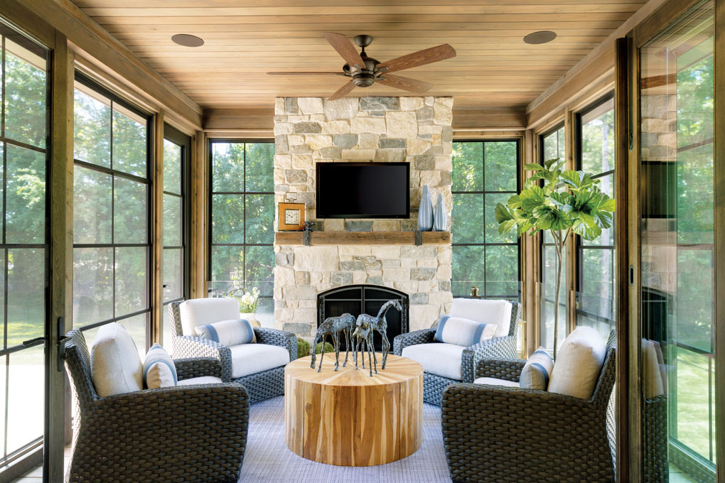 A spacious porch is filled with a stone fireplace, wooden coffee table and wicker chairs. The walls are made of floor-to-ceiling windows that look out onto the spacious backyard.