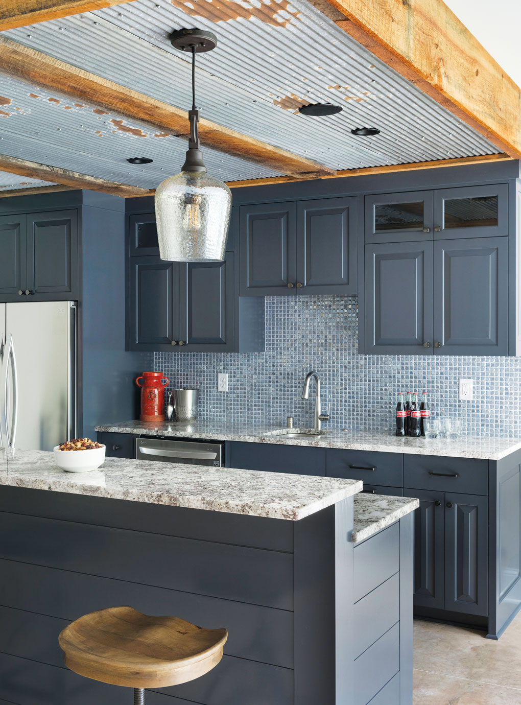 A bar in the lower level of a home features a tin ceiling and a custom bar topped with granite.