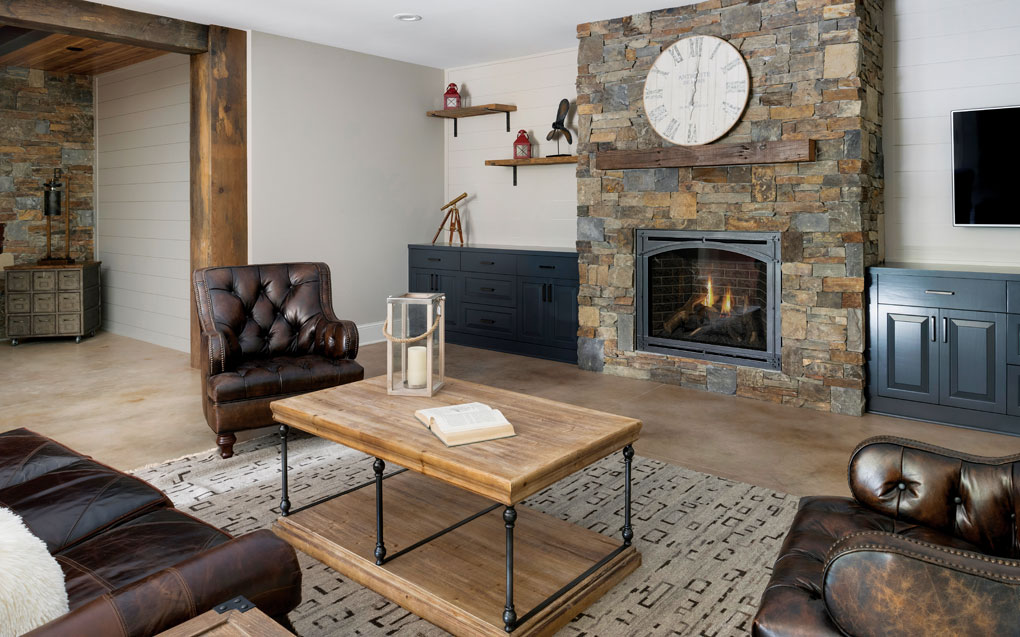 A basement is furnished with a leather sofa and chairs surrounding a coffee table that are set next to a large floor-to-ceiling, stone fireplace.