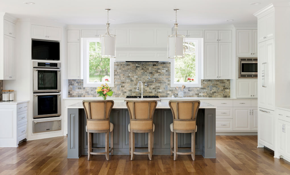A kitchen with wood floors, quartz countertops, a center island with seats, stone backsplash, white cabinetry and stainless steel appliances.