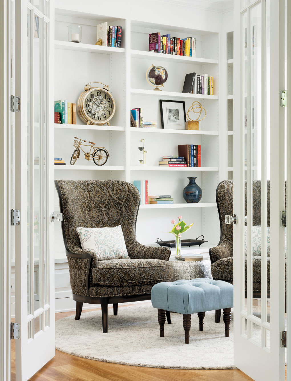A personal library boasts floor-to-ceiling bookshelves and a chair to relax in.