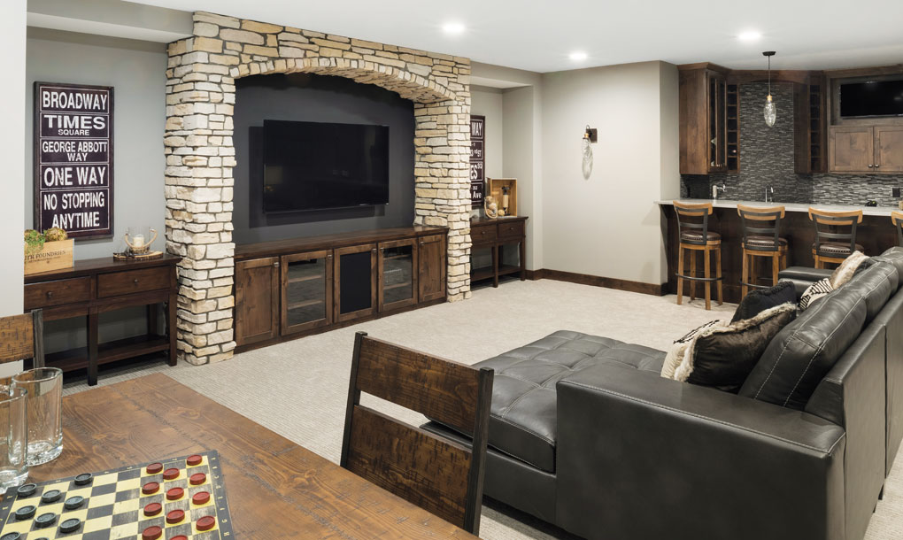 A basement with a bar and leather sofa are set beside a stone arch housing a mounted television.