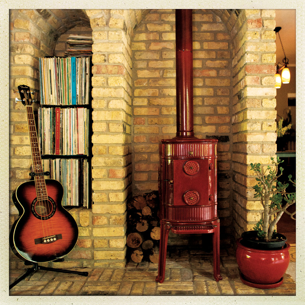 A vinyl collection in nooks near a red lacquer wood-burning stove surrounded by Chicago brick.