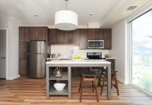 modern kitchen with brown cabinets and center island with backless stools
