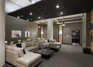 interior shot of entertainment room with two sectionals and coffee tables, backed by cocktail tables