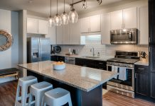 kitchen with modern appliances and stools at a granite kitchen island