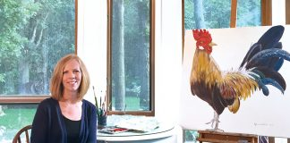 A portrait of Bonnie Folkerts with a painting of a rooster next to her.