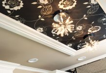 A black wallpaper with a floral pattern accents a ceiling.