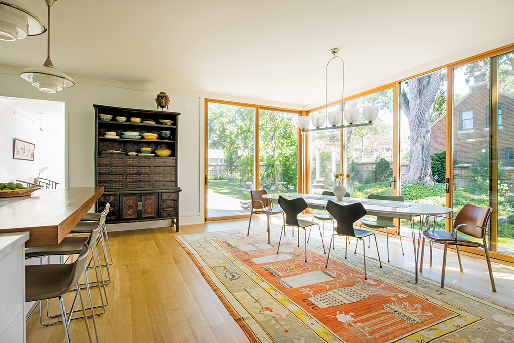 A dining room flooded with natural light thanks to large windows looks out onto a spacious backyard.