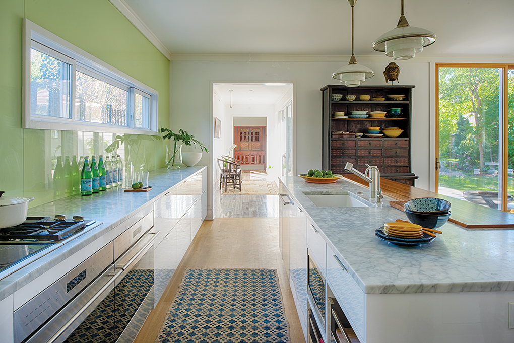 A kitchen features clean lines with marble countertops, no upper cupboards, a center island, stainless steel appliances and wood floor.