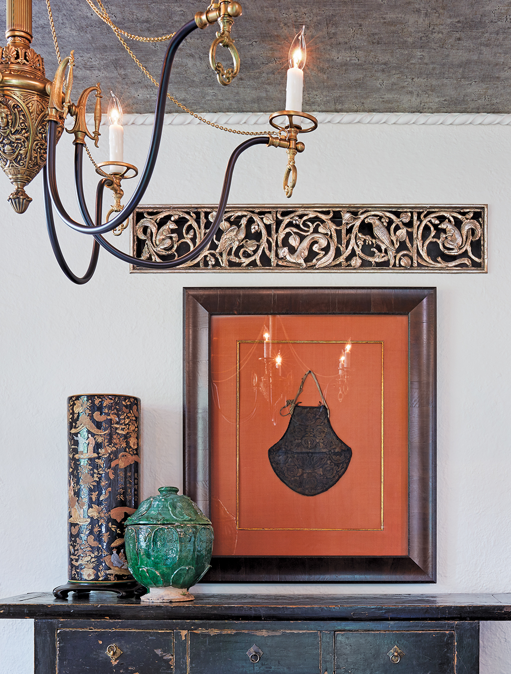 A Chinese peasant bag sits framed above a table. In the foreground is an ornate chandelier.